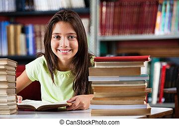 colegiala, sonriente, mientras, sentado, con, montón libros, en, biblioteca