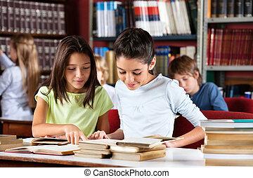 colegialas, libro de lectura, juntos, en la mesa, en, biblioteca
