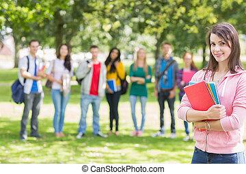 colegio, niña, tenencia, libros, con, estudiantes, en el estacionamiento