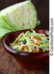 Coleslaw salad in white bowl on a brown background