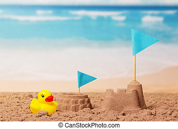 Coliseum and Tower of sand, blue flag, rubber duck on beach.