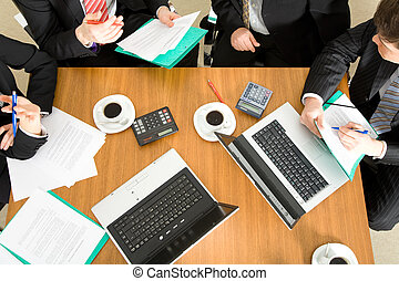 Collaboration - Four people discussing or negotiating a...