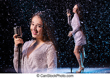 Collage beautiful young woman with long hair in an evening dress sings into a vintage microphone. Singer against the background of falling snow in a dark studio. Close up.