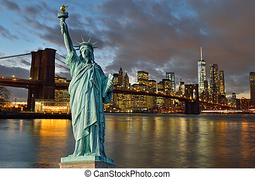 Manhattah skyline with Brooklyn Bridge at night and Statue...