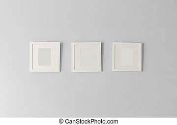 Collage of three white photo frames on the wall