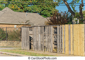 Collapsed aged wooden fence near new lumber boards installation at suburban house in Texas, USA