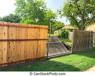 Collapsed aged wooden fence near new lumber boards installation of suburban residential house