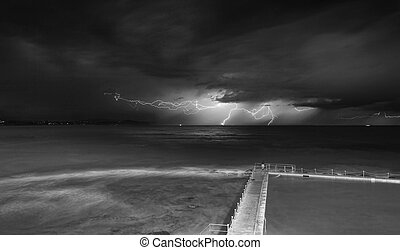 Views from Collaroy over the rockshelf and rockpool south of the beach towards the north east at the storms. Seeking shelter from the rain to capture this long exposure and yes that little figure was stretching and exercising in the rain..