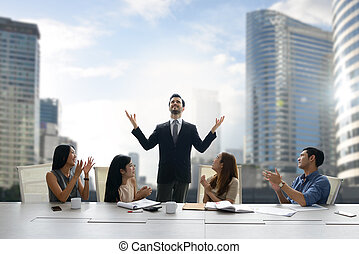 Colleagues applauding proud businessman in a team meeting