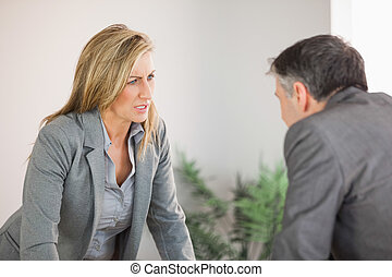 Colleagues arguing in an office - A blonde businesswoman...