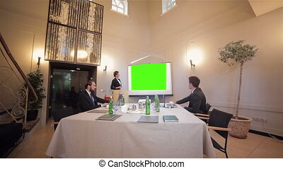 Colleagues asking a question to a businesswoman during a...