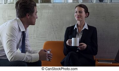 Colleagues chatting on coffee break in modern business...
