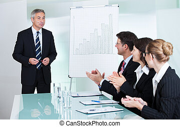 Diverse business colleagues seated around a table clapping after a staff presentation by a manager or senior executive