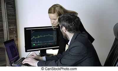 colleagues discuss currency changing on a stock exchange. watching currency exchange chart at laptop