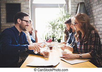Colleagues from work socializing in restaurant and eating togeth