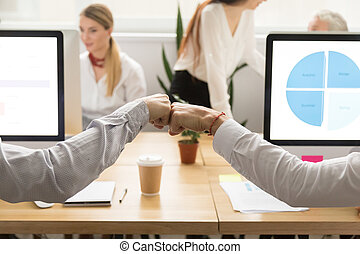 Colleagues giving fist bump, corporate teamwork concept, close u