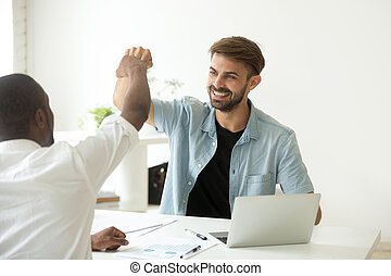 Colleagues giving fist bumps after reaching shared business goal