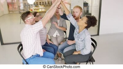 Colleagues giving high-five - Group of colleagues in casual...