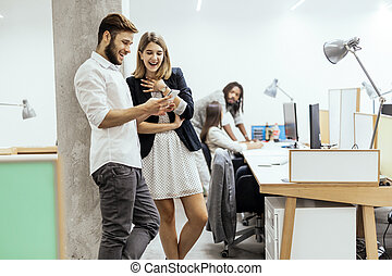 Colleagues in office using phones and smiling