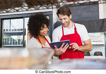 Colleagues in red apron using tablet