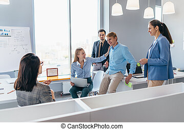Colleagues lively discuss business issues together in the office