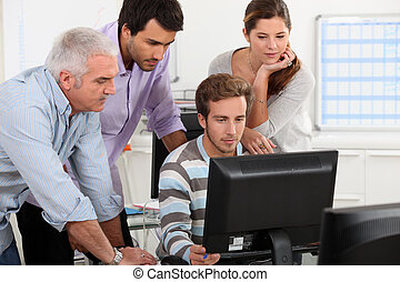 Colleagues looking at computer