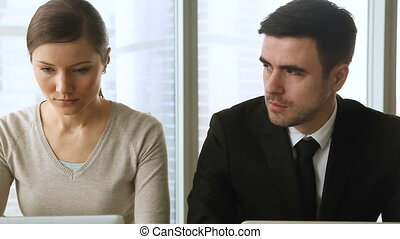 Colleagues looking at each other with contempt and dislike, rivalry