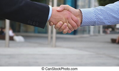 Colleagues meet and shake hands in the city background. Two...