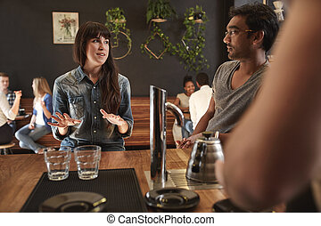 Colleagues of mixed races talking at coffee shop counter -...