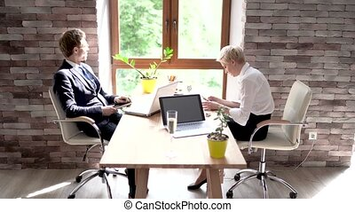 Colleagues of the Case Man and Woman Sit in the Office at the Desk After a Business Meeting.