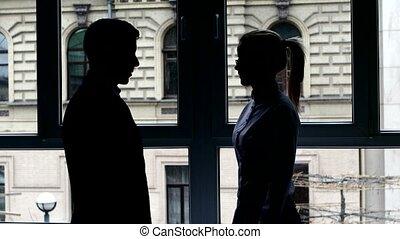 Colleagues shaking hands and contract. Man accompanies the girl to the entrance. The action takes place in the office. Silhouette