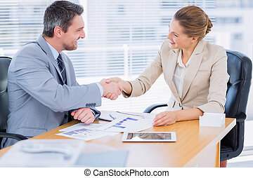 Colleagues shaking hands in a business meeting at office desk