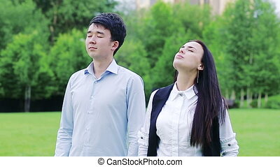 Colleagues taking deep breaths in the park with eyes closed