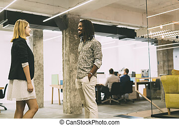 Colleagues talking in office and smiling