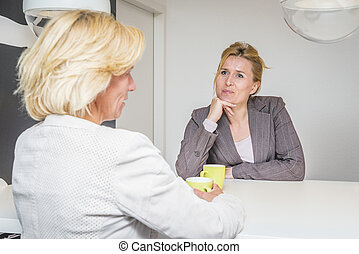 Colleagues talking in the coffeebreak - Two woman talking...