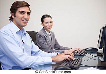 Colleagues using computers at office