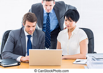 Colleagues using laptop at office desk