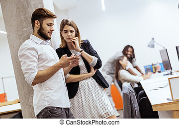 Colleagues using phone in an office