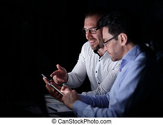 colleagues using smartphones while sitting at a Desk. ...