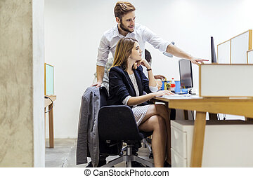 Colleagues working on a PC in an office