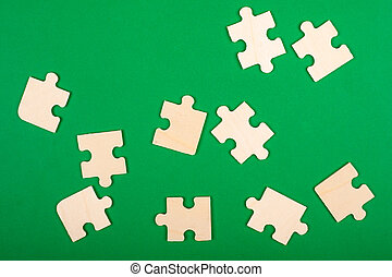 collect puzzles. puzzle pieces scattered on a green background