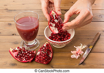 Collecting pomegranate seeds - Hands of a woman collecting ...