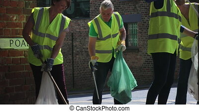 A group of five mature adults clearing up the streets as they collect litter.