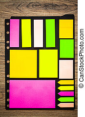 Collection colored sticky notes on wooden desk.