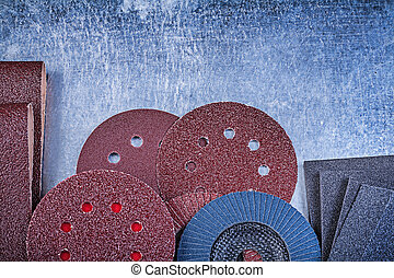 Collection of abrasive tools on metallic background top view