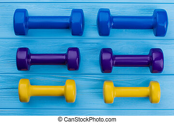 Collection of colorful dumbbells on wooden background.