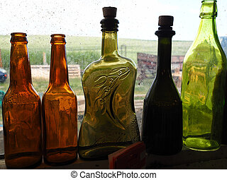 Collection of colorful glass bottles in a window