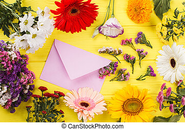 Collection of different flowers and post mail. Yellow wooden...