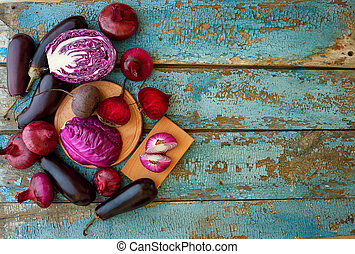 Collection of fresh purple vegetables on the blue wooden background