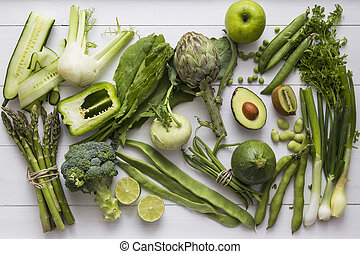 Collection of green fruit and vegetable ingredients, including cucumber, fennel, asparagus, broccoli, bell pepper, artichoke, kohlrabi, beans, peas, lime, courgette/zuchini, avocado, kiwi, apple, herbs and spring onion.